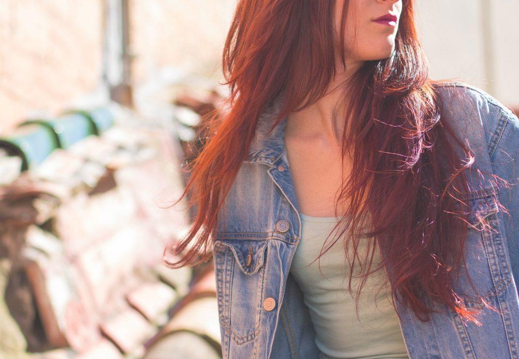 Frau mit langen roten Haaren und Jeansjacke