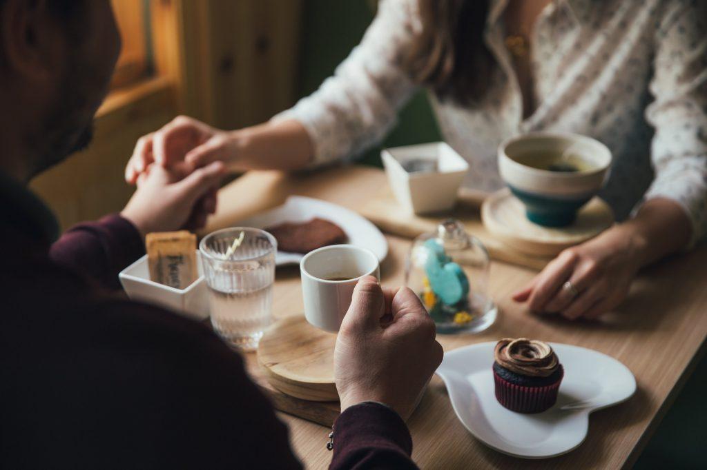 Mann und Frau halten Händchen beim Kaffee trinken