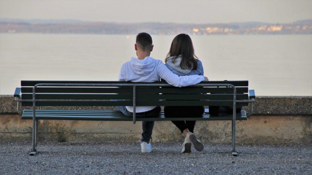 Junges Paar sitzt auf einer Bank beim ersten Date