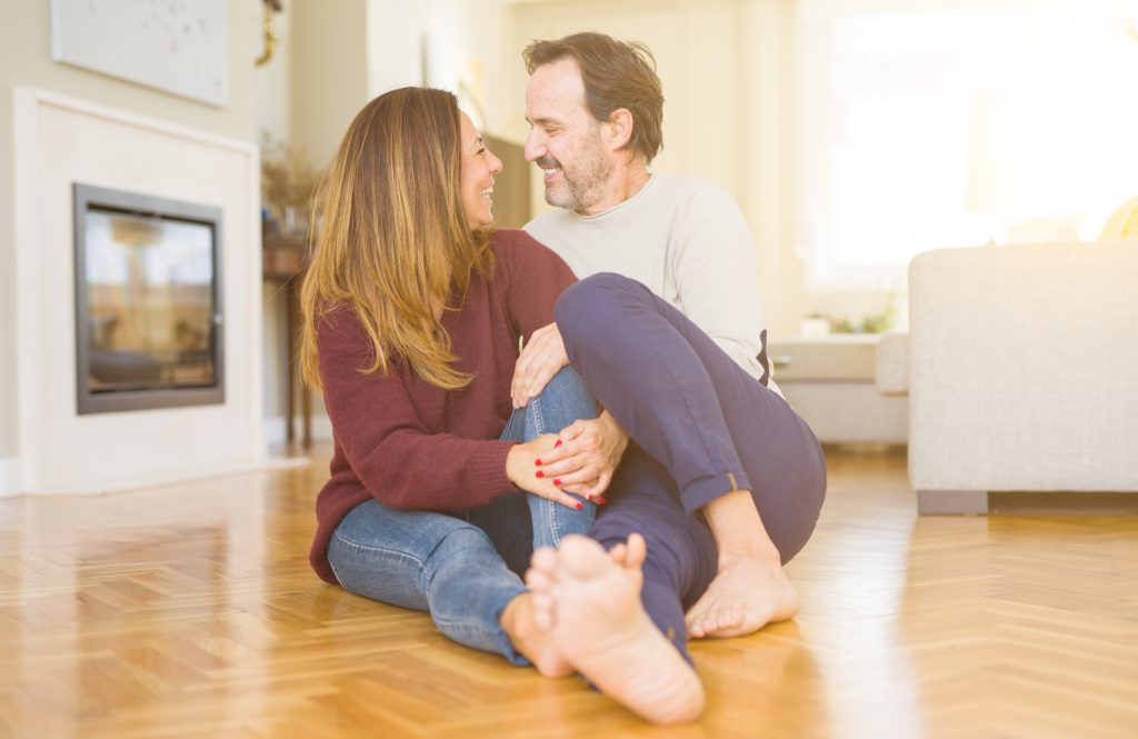 Paar sitzt barfuß auf dem Fußboden im Wohnzimmer und lacht sich an.