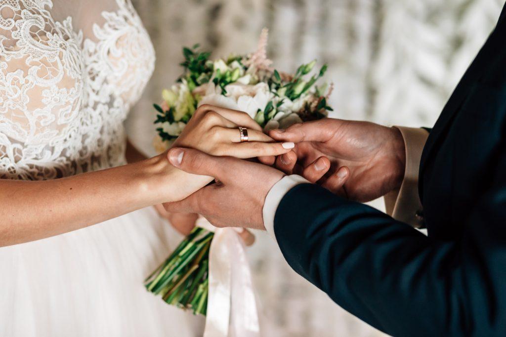 Die verschlungenen Hände von Braut unf Bräutigam mit Hochzeitsstrauß