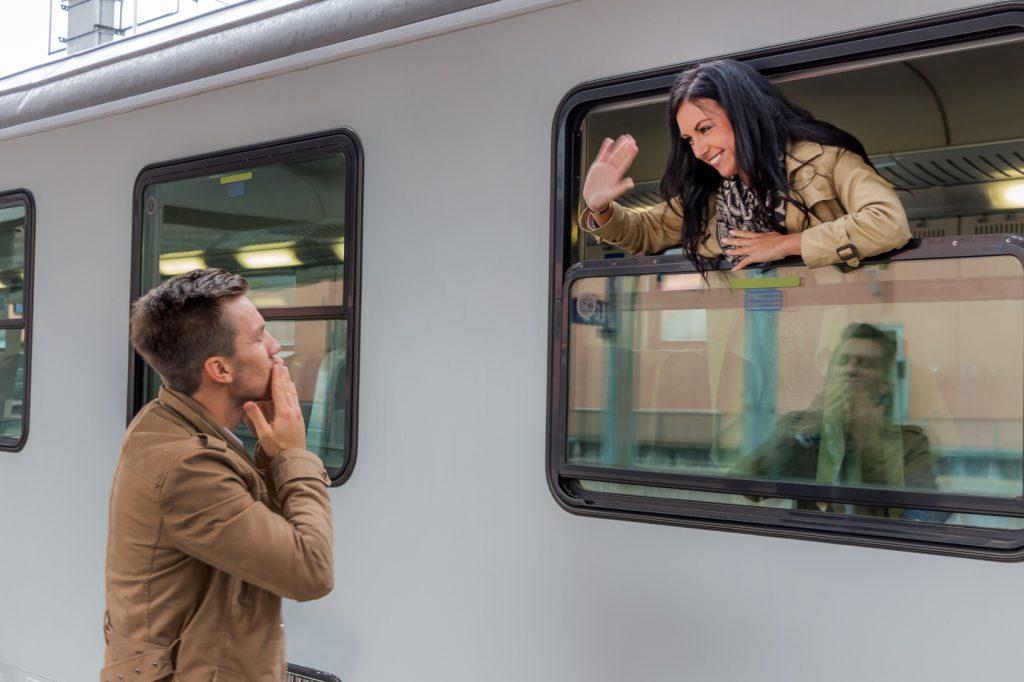 Frau ist im Zug und verabschiedet sich von Ihrem Mann