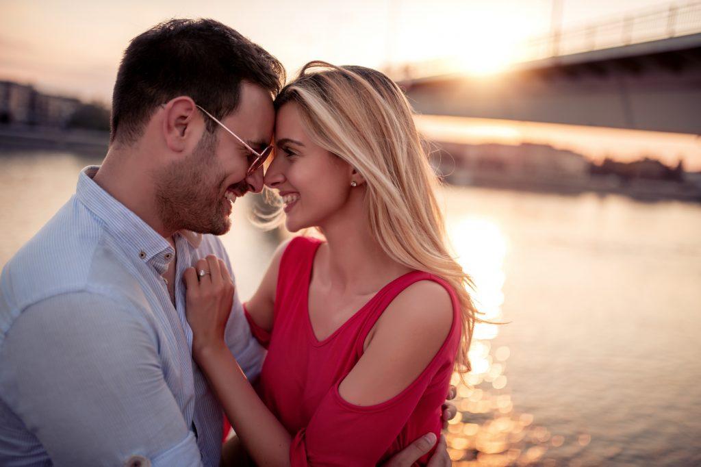 Verliebstes Paar hält sich lächelnd im Arm bei Sonnenuntergan