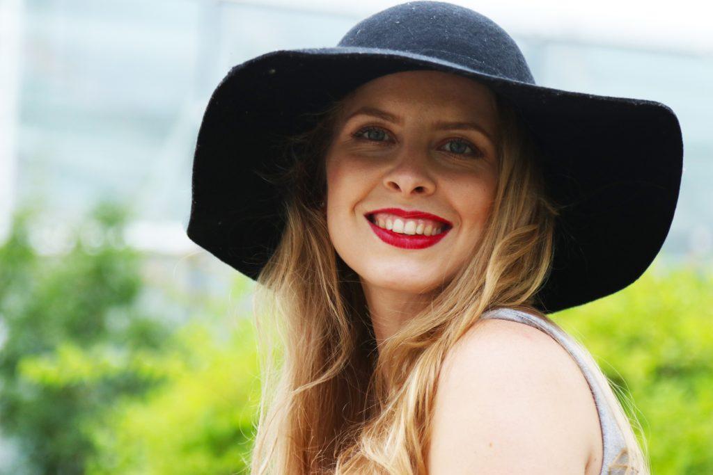Lachend, junge Frau, mit langen blonden Haaren und schwarzem Hut.