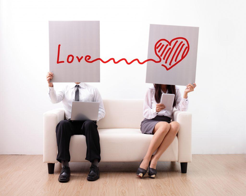 Mann und Frau sitzen auf einem weißen Sofa, die Gesichter sind mit weißen Schildern verdeckt, auf welchen in rot Love verbunden mit einem Herz steht.