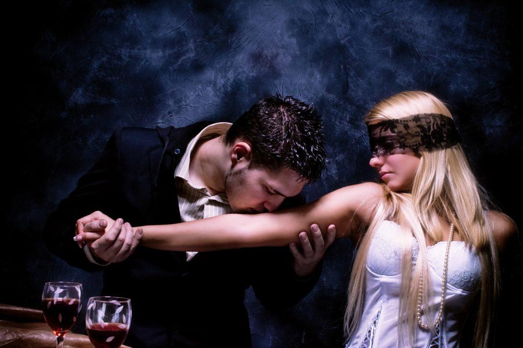 Dunkelhaariger Mann küsst den Arm einer blonden Frau, erotische Fantasie kann mit Cyber-Sex virtuell umgesetzt werden