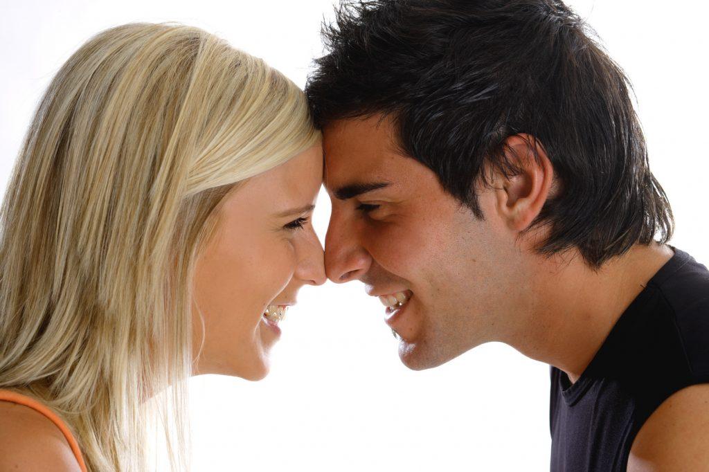 Blonde Frau und dunkelhaariger Mann lehnen Kopf an Kopf und lachen sich an.