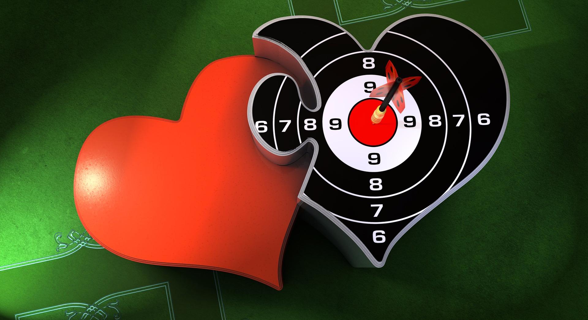 Zwei Herzen, ein rotes und eines in Form einer Zielscheibe, sind nach dem ersten date ineinander verschlungen
