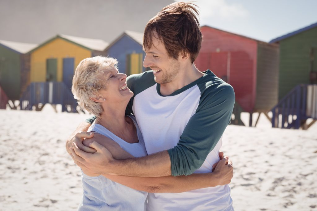 Frau mittleren Alters verliebt Arm in Arm mit jungen Mann