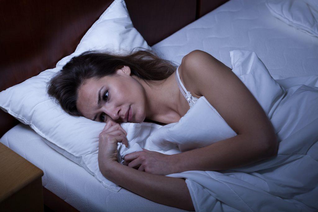 Frau liegt wach im Bett und macht sich Sorgen
