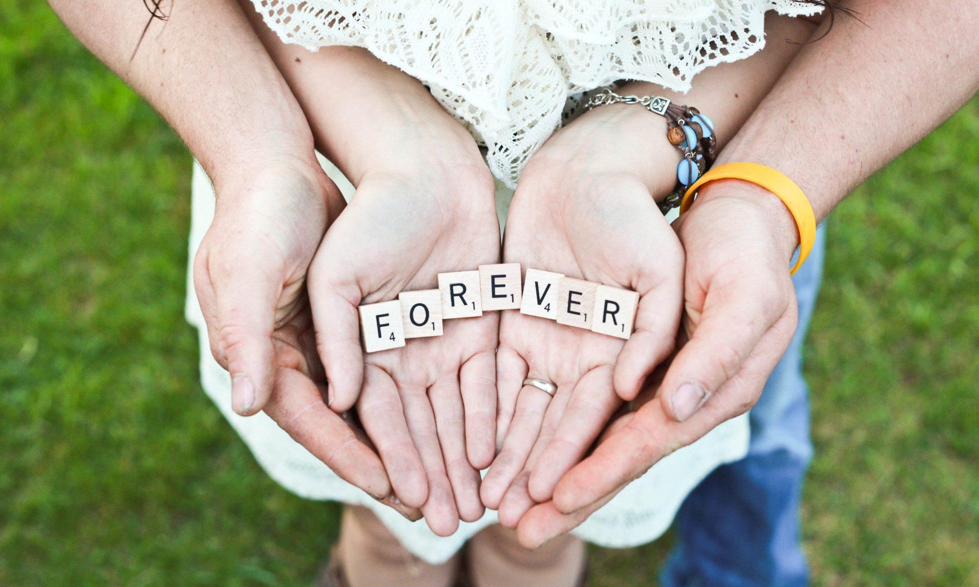 Vier Hände liegen ineinander mit dem Wort Forever