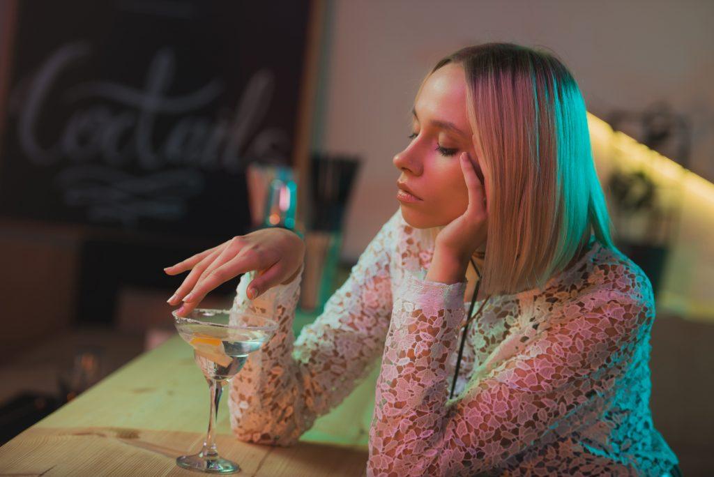 Junge, attraktive Frau sitzt gelangweilt und alleine an der Bar