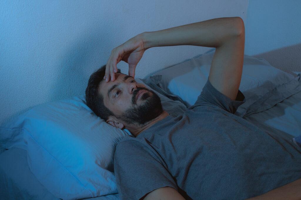 Mann liegt mit Schlafstörung wach im Bett