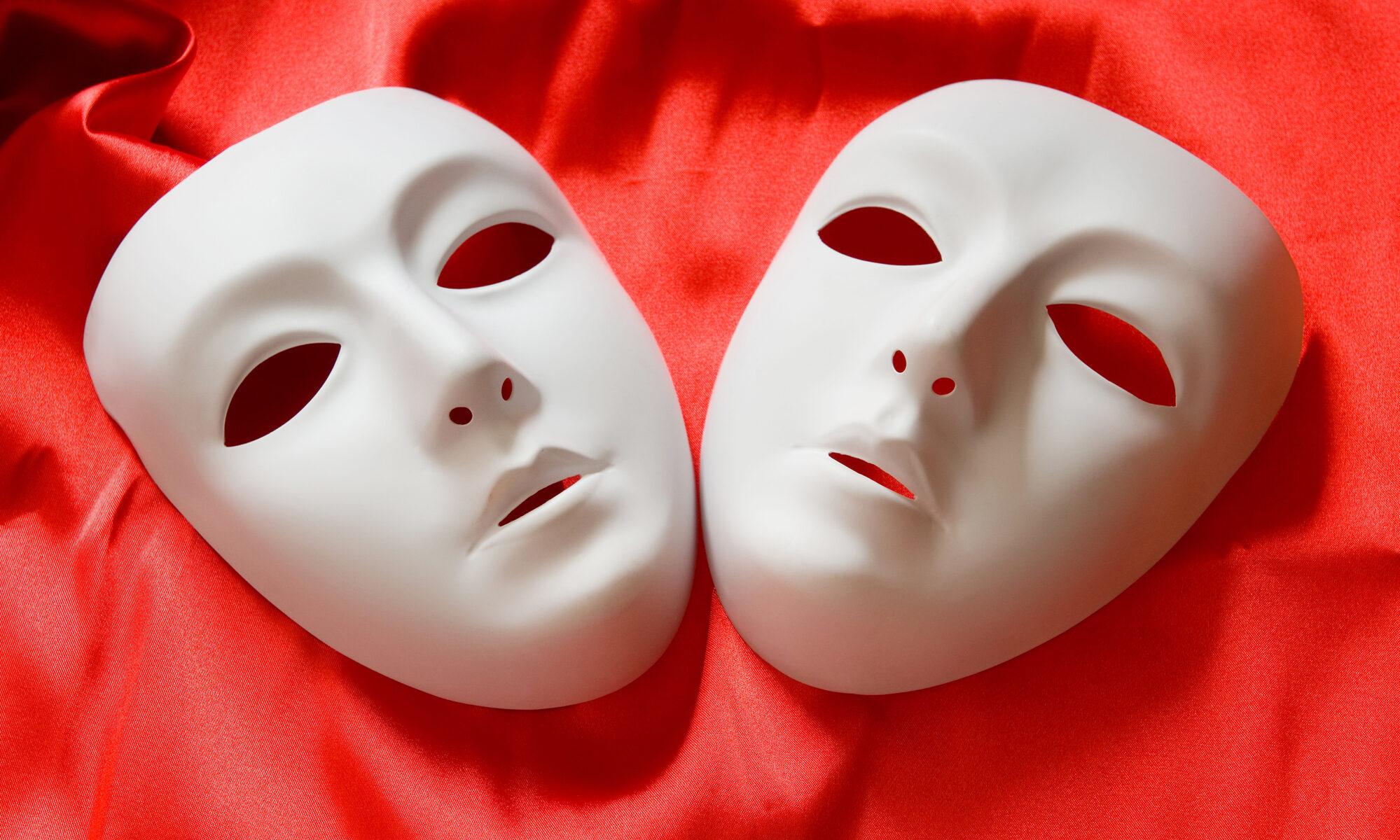 Zwei gefühlslose Masken auf roten Stoff