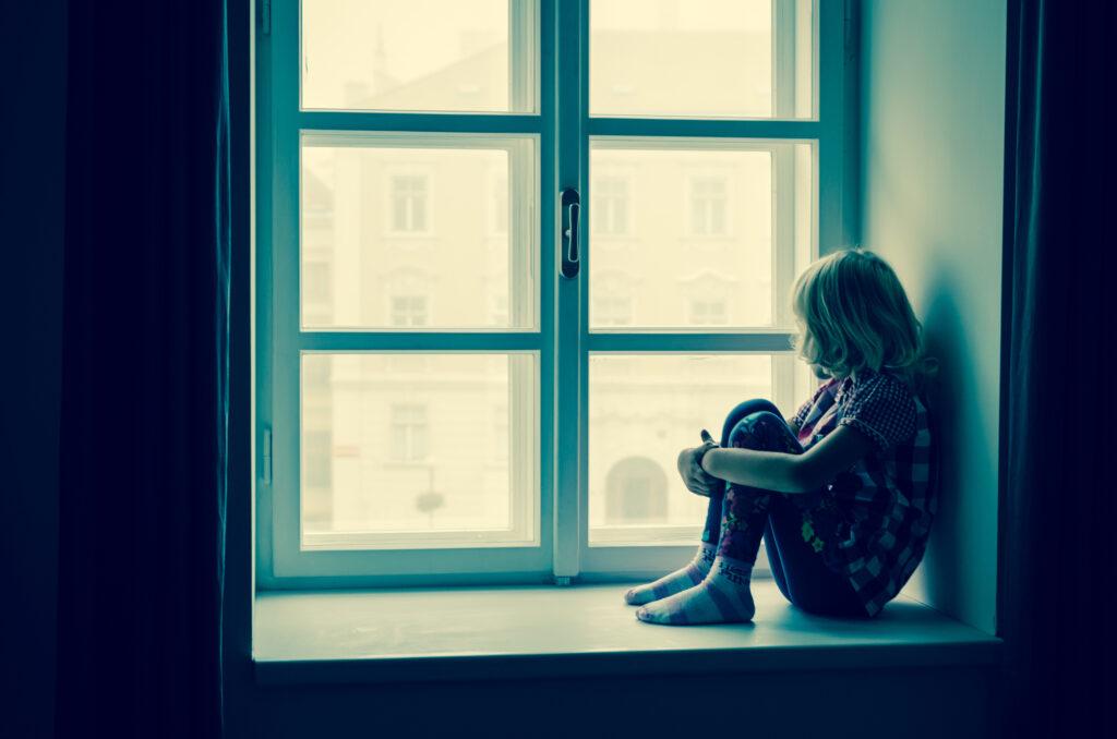 Kind sitzt einsam und verlassen auf der Fensterbank