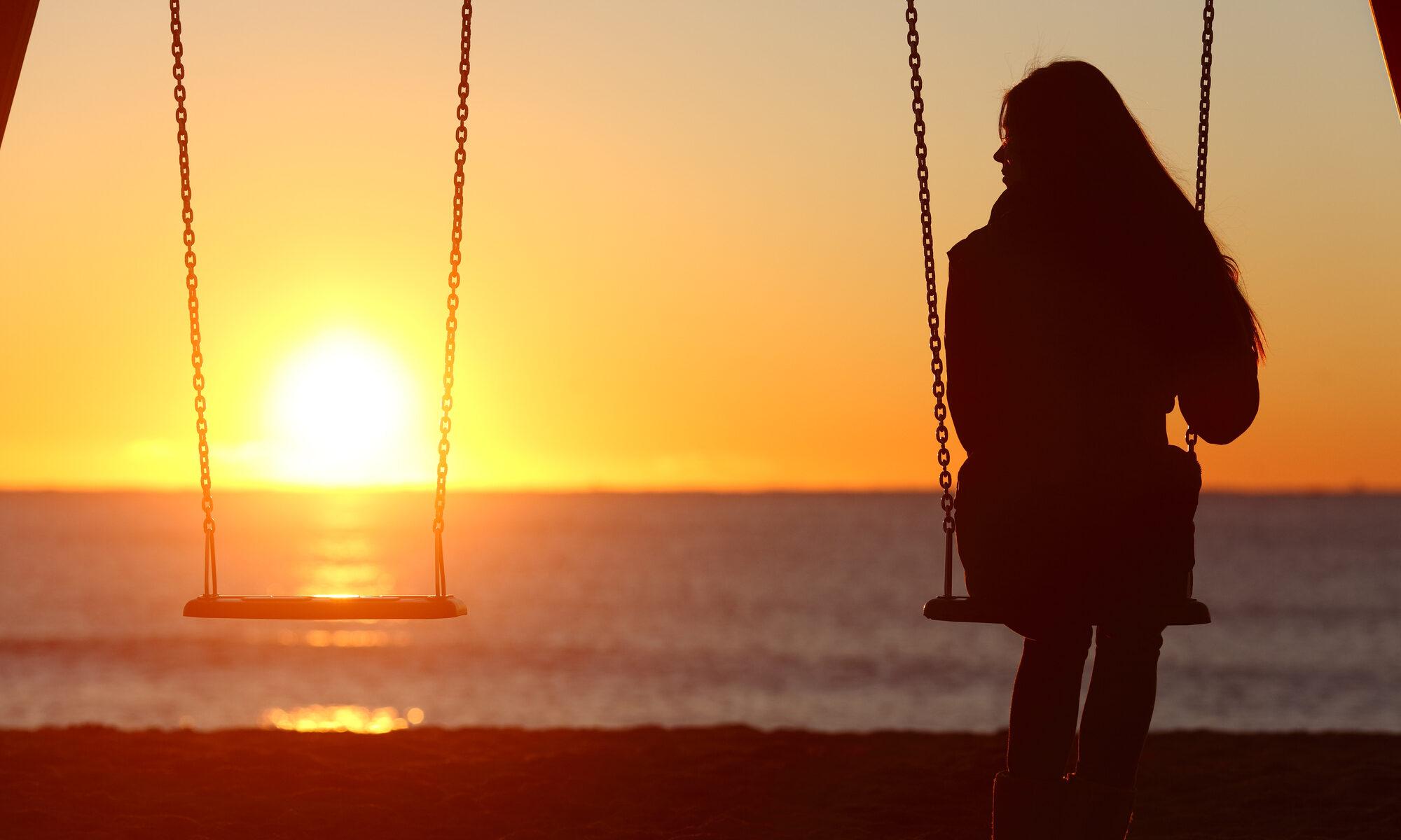 Frau sitzt alleine voller Sehnsucht auf einer Schaukel im Sonnenuntergang