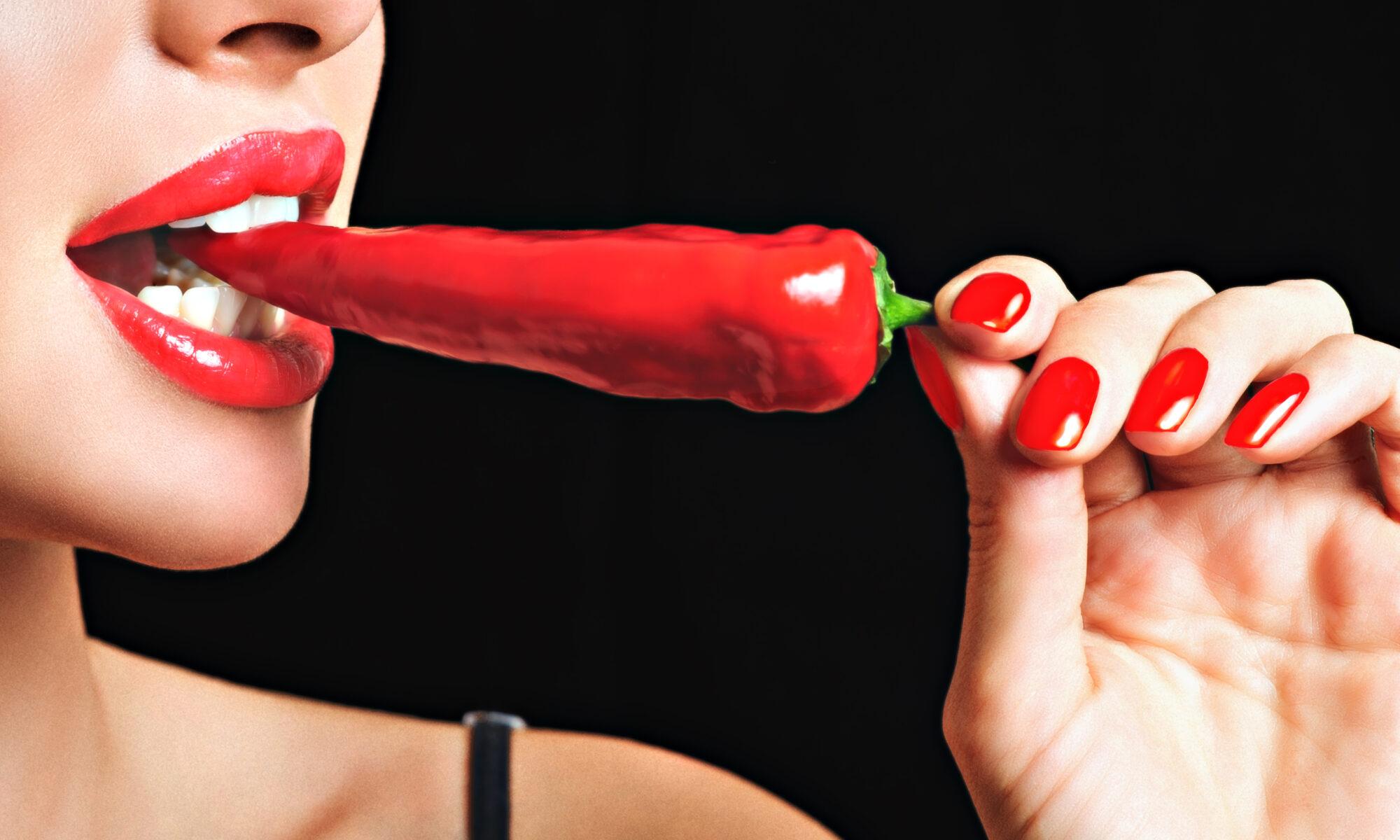 Frau mir roten Lippen beißt auf rote Pepperoni