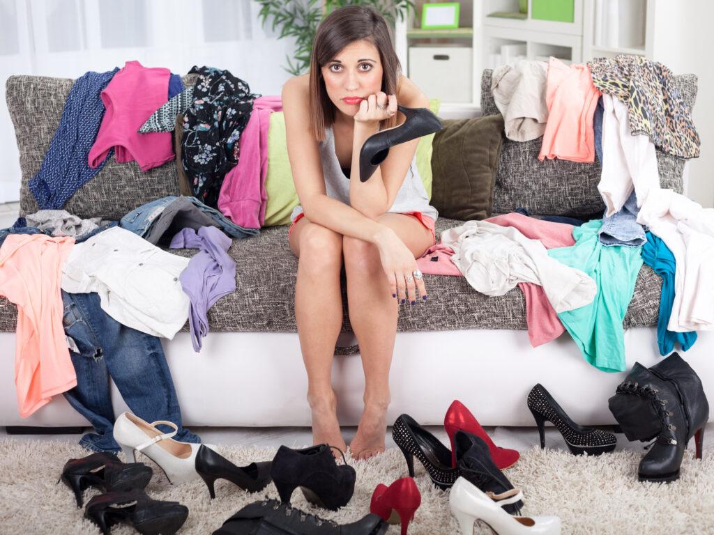 Frau im Kleidungsberg und weiß nicht was sie anziehen soll