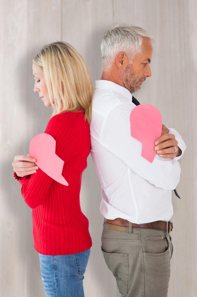 Mann und Frau stehen Rücken an Rücken mit gebrochenem Herzen