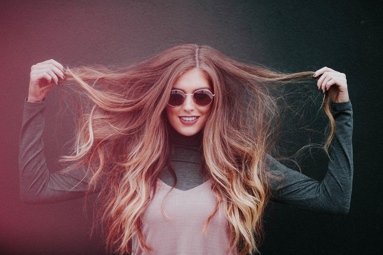 Frau die Ihre Langen Haare in den Fingern hält