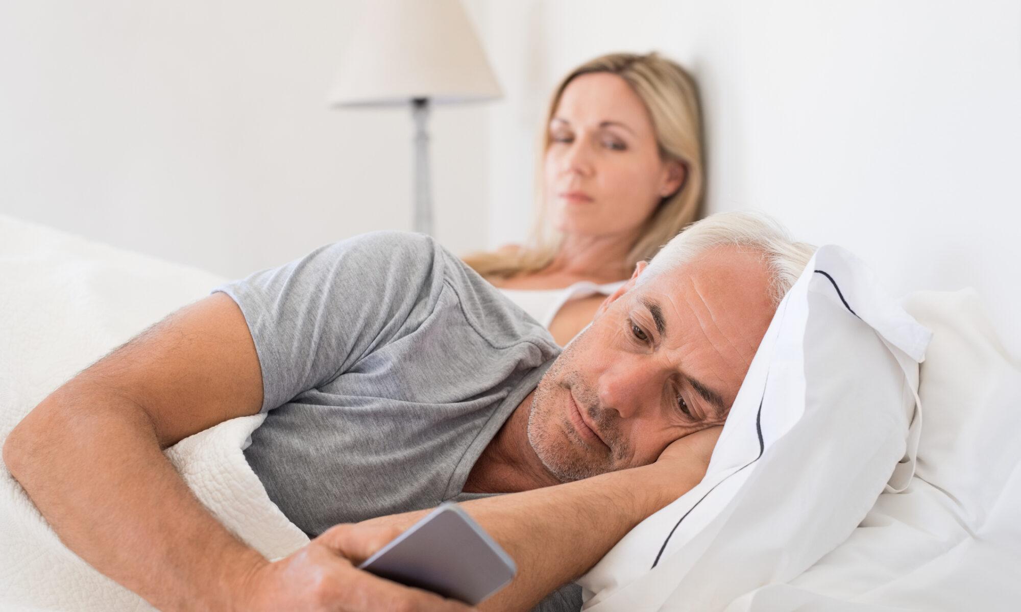 Frau beobachtet Mann im Bett, der heimlich am Handy ist