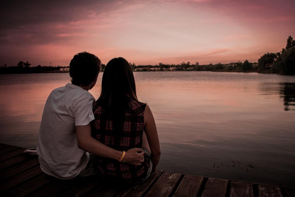 Verliebtes Paar sitzt bei Sonnenuntergang am Wasser