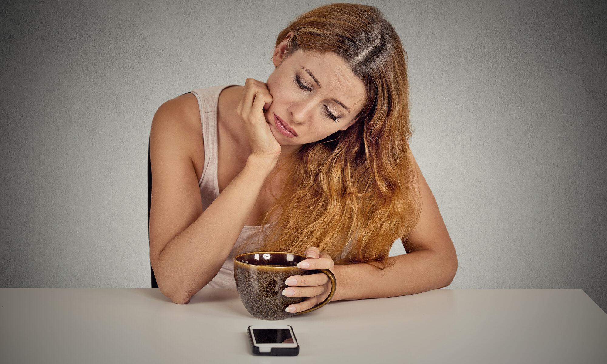 Frau sitzt wartent vor dem Handy